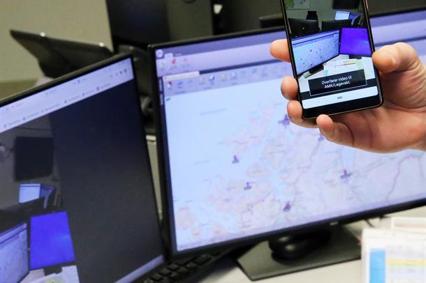 Bilde av mobiltelefon som holdes opp foran skjermene til AMK-operatøren.